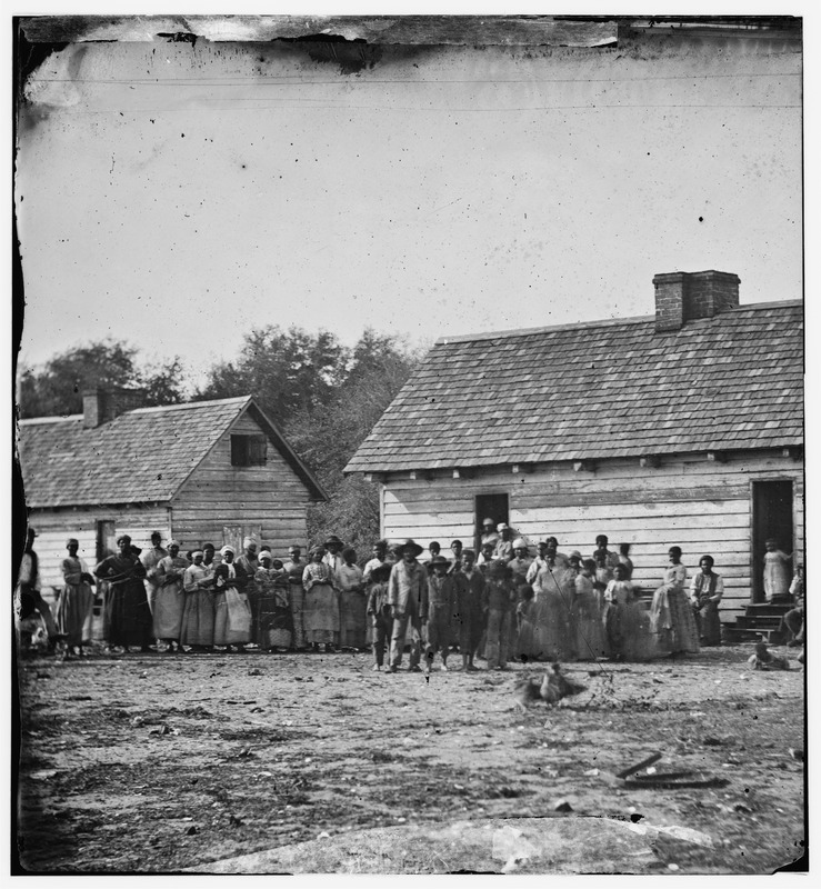 The Prints and Photograph Division of the Library of Congress has two slightly different negatives of this scene by Timothy H. O'Sullivan, the Civl War photographer. Sullivan visited Smith's plantation in 1862 and made several photographs of its enslaved population. In general he left no records of his experiences and photographs, and the only identifiers are to be found on the notes or captions he scribbled on his negatives; in this particular case, on the negative sleeve O'Sullivan wrote group on J.J. Smith's Plantation, Beaufort, S.C. For details on O'Sullivan and his photographs, see James Horan, Timothy O'Sullivan: America's Forgotten Photographer (New York, 1966) and Joel Snyder, American Frontiers: The Photographs of Timothy H. O'Sullivan (New York, 1981). See also image NW0243 on this website.