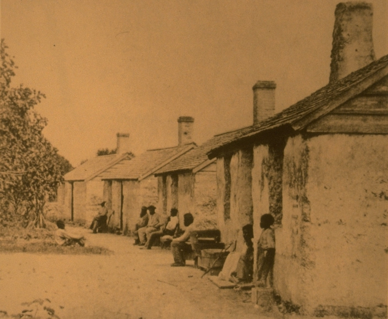 Shows emancipated men, women, and children in front of their houses; chimneys and shingled roofs.
